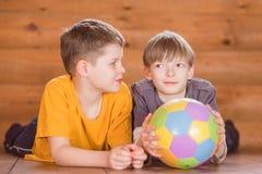 Deux amis avec une boule se trouvant sur le plancher Images libres de droits