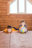 Deux amis avec une boule se trouvant sur le plancher Photo stock