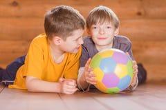 Deux amis avec une boule se trouvant sur le plancher Photo libre de droits