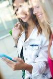 Deux amis ayant l'amusement avec des smartphones Image stock