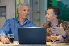 Deux amis ayant la boisson et regardant l'ordinateur portable Image stock