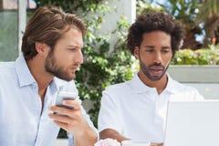 Deux amis ayant le café ainsi que l'ordinateur portable Images libres de droits