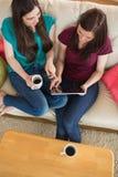 Deux amis ayant le café sur le divan et à l'aide du comprimé Photo libre de droits