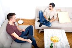 Deux amis ayant une conversation dans le salon Photos stock