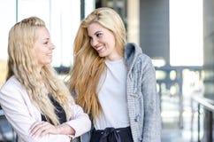 Deux amis blonds d'étudiants riant utilisant le téléphone portable et le comprimé Image libre de droits