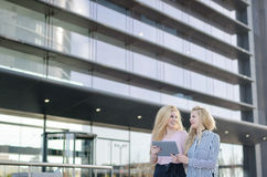Deux amis blonds d'étudiants riant utilisant le téléphone portable et le comprimé Photo libre de droits
