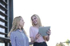 Deux amis blonds d'étudiants riant utilisant le téléphone portable et le comprimé Photos stock