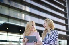 Deux amis blonds d'étudiants riant utilisant le téléphone portable et le comprimé Images libres de droits