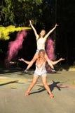 Deux amis blonds heureux de femme ayant l'amusement avec éclater Holi PO Image stock