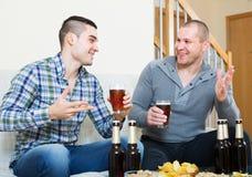 Deux amis buvant de la bière à la maison Photographie stock libre de droits