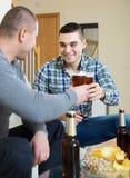 Deux amis buvant de la bière à la maison Photos libres de droits