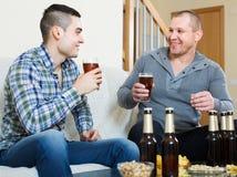 Deux amis buvant de la bière à la maison Images stock