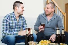 Deux amis buvant de la bière à la maison Photos stock