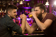 Deux amis buvant de la bière et ayant l'amusement au bar Image stock