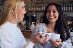 Deux amis buvant du café au café pendant la conversation Photographie stock libre de droits