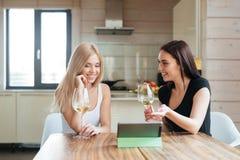 Deux amis buvant du vin et regardant la tablette Photographie stock