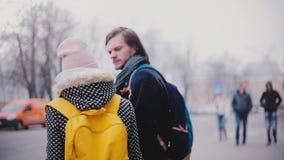 Deux amis caucasiens décontractés heureux, homme et femme, se tenant ensemble et parlant dans la rue le jour neigeux froid d'hive banque de vidéos
