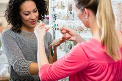 Deux amis choisissant des bijoux dans le magasin de mode Photo stock
