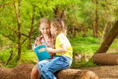 Deux amis chuchotant des secrets se reposant au parc Image libre de droits