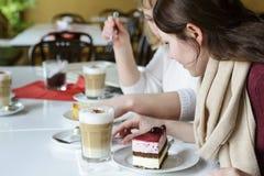 Deux amis communiquent avec la nourriture, boivent du café et mangent le gâteau Photo stock