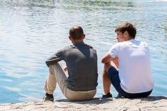 Deux amis communiquent par la rivière Photographie stock