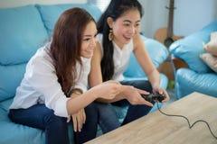 Deux amis concurrentiels de femmes jouant les jeux vidéo et l'ha enthousiaste Photo stock