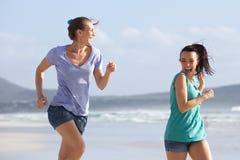 Deux amis courant en été à la plage Images libres de droits