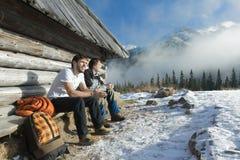 Deux amis détendant sur le banc en bois en montagnes d'hiver dehors Photographie stock