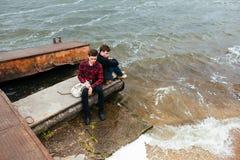 Deux amis détendant sur le pilier Photographie stock