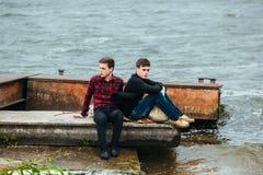 Deux amis détendant sur le pilier Photo stock
