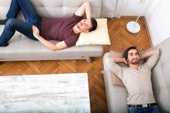 Deux amis détendant sur le sofa Photos libres de droits
