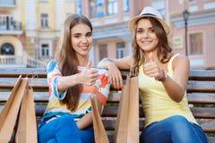 Deux amis détendant sur un banc pendant les achats Image libre de droits