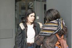 Deux amis d'étudiant parlant dans la rue Photographie stock libre de droits