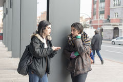Deux amis d'étudiant parlant dans la rue Photographie stock