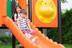 Deux amis d'enfants ayant l'amusement à jouer ensemble sur la glissière du ` s d'enfants Image stock
