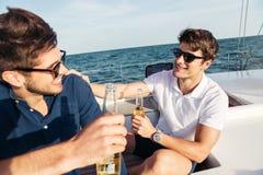 Deux amis d'hommes buvant de la bière tout en se reposant sur le yacht Images stock