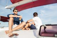 Deux amis d'hommes buvant de la bière tout en se reposant sur le yacht Image stock