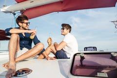 Deux amis d'hommes buvant de la bière tout en se reposant sur le yacht Images libres de droits