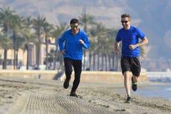 Deux amis d'hommes courant ensemble sur le sable de plage avec les palmiers m Photographie stock libre de droits