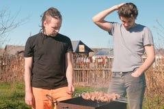Deux amis d'hommes font cuire la viande de shashlik sur le gril de charbon de bois sur l'arrière-cour Parler et sourire ensemble Image stock