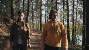 Deux amis d'hommes marchant sur le sentier piéton en bois le jour ensoleillé banque de vidéos