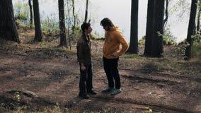 Deux amis d'hommes se tenant sur des bois sentier piéton et querelles le jour ensoleillé banque de vidéos