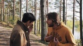 Deux amis d'hommes se tenant sur la voie et les débuts de forêt discutant le jour ensoleillé banque de vidéos