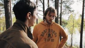 Deux amis d'hommes se tenant sur la voie et les débuts en bois discutant le jour ensoleillé banque de vidéos