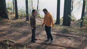 Deux amis d'hommes se tenant sur le sentier piéton de forêt et discutant le jour ensoleillé clips vidéos