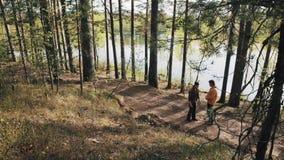 Deux amis d'hommes se tenant sur le sentier piéton et les querelles de forêt le jour ensoleillé banque de vidéos