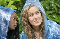 Deux amis d'université dans des couches de pluie Photographie stock