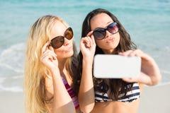 deux amis dans des maillots de bain prenant un selfie Photo stock
