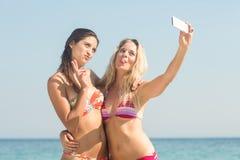 deux amis dans des maillots de bain prenant un selfie Photos stock
