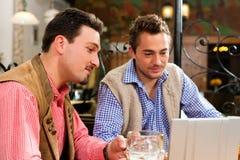 Deux amis dans le pub bavarois avec l'ordinateur portatif Image libre de droits